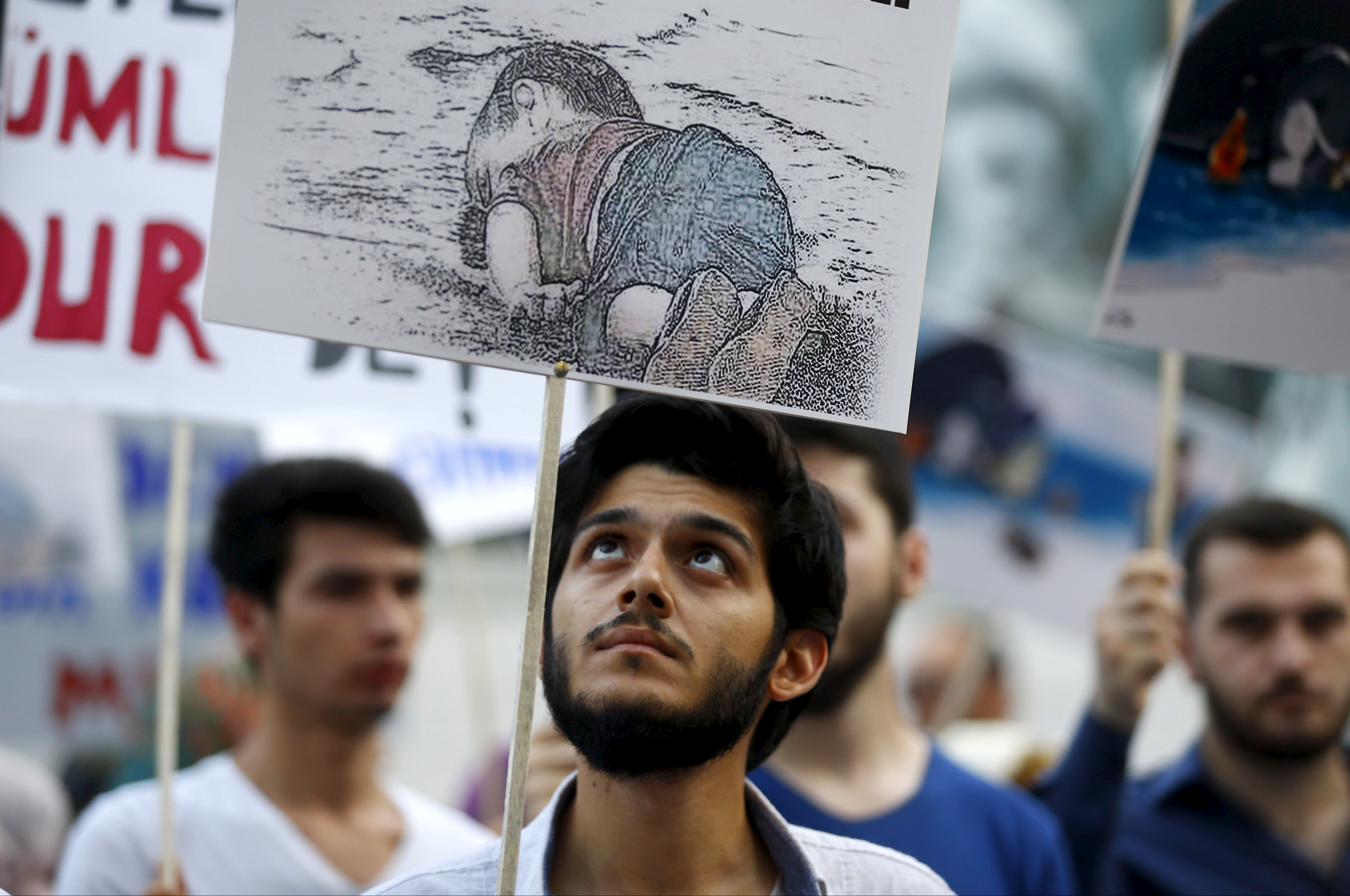 A man holds a poster with a drawing depicting a drowned Syrian toddler during a demonstration for refugee rights in Istanbul